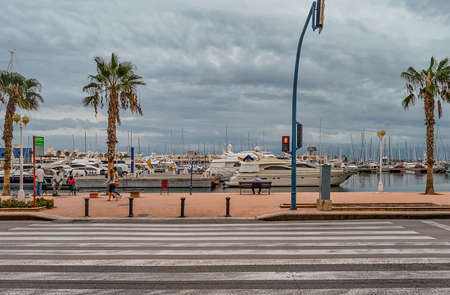 Alicante, Spain - September, 29, 2015: Pedestrian crossing to embankment of Alicante port in autumn overcast day, Spain.