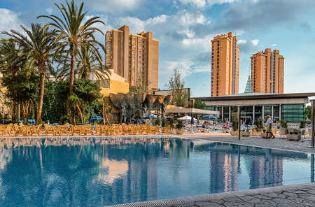 Benidorm, Spain - October, 1, 2015: Tourist area in famous european Spanish resort Benidorm with pool, street cafe and tropical plants in autumn.
