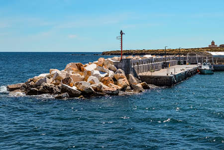Tabarca Island, Alicante, Spain - May, 14, 2016: Pier of Tabarca Island with barrier for waves in shape of stone heap in Mediterranean Sea. Tabarca located close to Santa Pola, Alicante.
