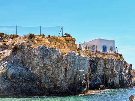 Rock cliff with building in bay of Mediterranean sea in sunny day. Stok Fotoğraf