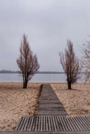 Wooden pathway on sand leading to waterfront river in leaving autumn overcast day. Stok Fotoğraf