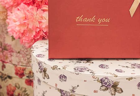 Red paper background with lettering 'thank you' among flowers and round floral boxes. Stok Fotoğraf