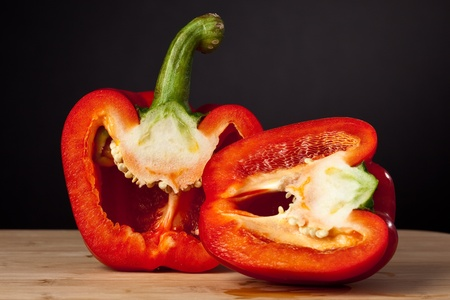 red bell pepper cut in half on a cutting board