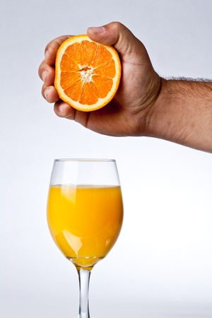 hand holding half an orange over a glass of juice Stock Photo