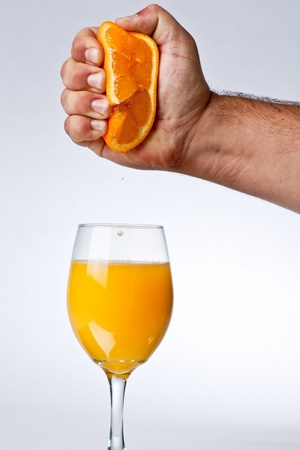 hand squeezing orange juice into a glass Stock Photo