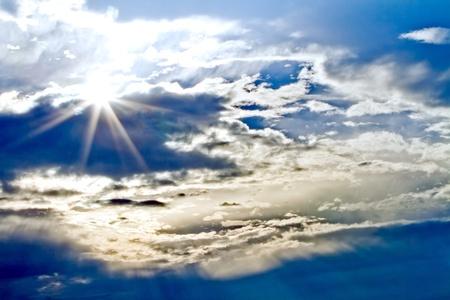 sunburst through the clouds with a blue sky