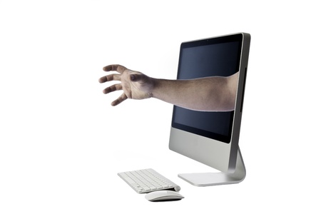 Modern looking all in one computer isolated against a white background with keyboard and mouse with a hand coming out of the screen indicating bullying