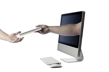 Modern looking all in one computer isolated against a white background with keyboard and mouse with a hand coming out of the screen handing a book to another hand