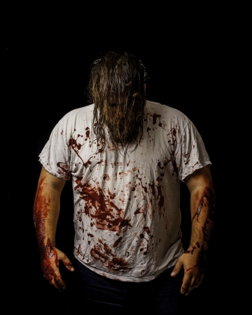 white male wearing a white shirt covered in blood with his hair covering his face.  Stock Photo - 16885629
