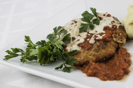 Close up shot of chicken parmesan with parsely garnish
