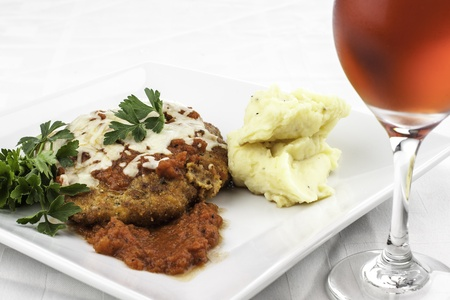 plate of chicken parmesan with mashed potatoes and red wine Stock Photo