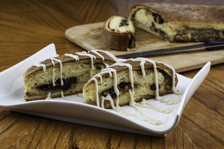 Nicely plated iced raisin nut bread with loaf and knife in backgound on wood cutting board photo
