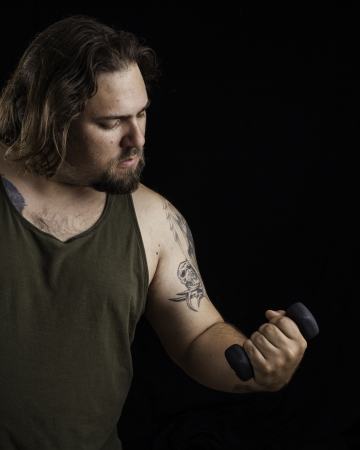 Humorus shot of a large man lifting a very small weight Stock Photo - 16885402
