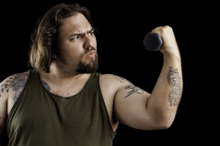 Humorus shot of a large man lifting a very small weight Stock Photo - 16885627
