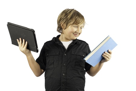 A young boy isolated on white holding a tablet pc and a book. Shows how times have changed.  photo