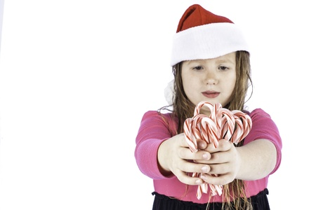young girl isolated on white with her hand outstretched holding candy canes