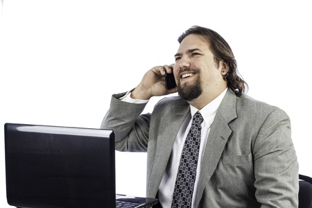 isolated shot of a business man at a laptop talking on a cell phone photo