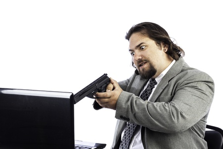 Business man with gun pointed at laptop could be used for anger or crime Stock Photo - 16885631