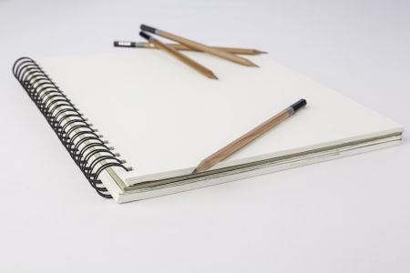 Clean blank pad of paper with pencil on white  with assorted pencils blurred in the back