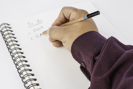 a mans hand holding a pencil making a list on white paper