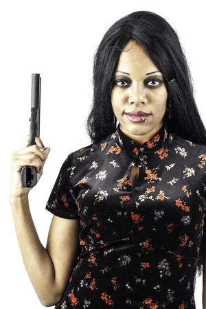 isolated black beautiful gothic woman holding a handgun in a beautiful dress. Sexy, seductive fashion look.  Stock Photo - 16885522