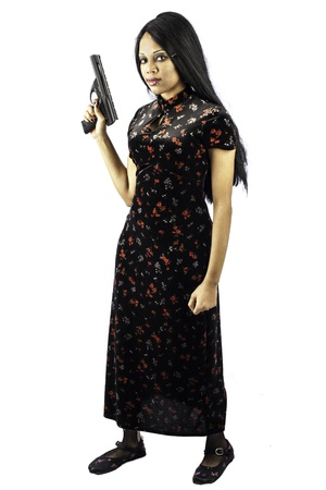 isolated black beautiful gothic woman holding a handgun in a beautiful dress. Sexy, seductive fashion look. Full length shot. Stock Photo - 16885520