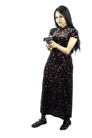 isolated black beautiful gothic woman holding a handgun in a beautiful dress. Sexy, seductive fashion look. Full length shot. Stock Photo