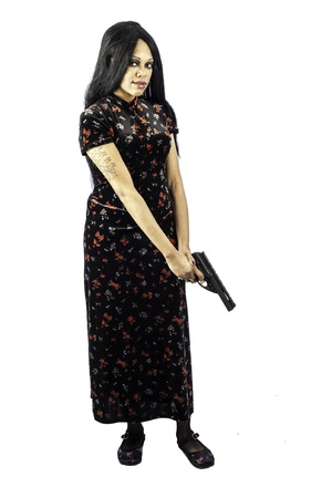 isolated black beautiful gothic woman holding a handgun in a beautiful dress. Sexy, seductive fashion look. Full length shot. Stock Photo - 16885518