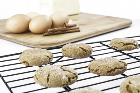 Molasses cookies cooling on a rack with ingredients blurred in the back
