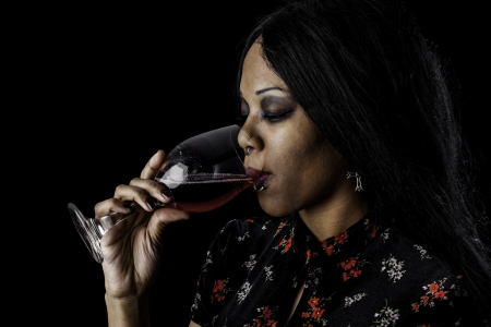 A sexy gothic african american drinking red wine from a glass against a dark background.  photo