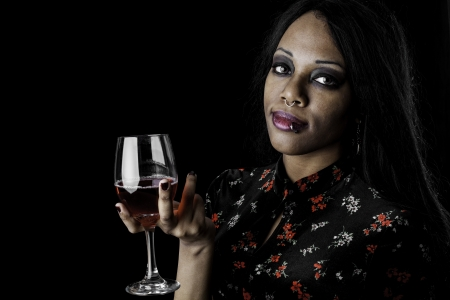 A sexy gothic african american holding a glass of wine against a dark background. Stock Photo - 16970309