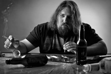 sad depressed man at a table with alcohol bottles, cigarettes and what looks like cocaine Stock Photo - 16970311