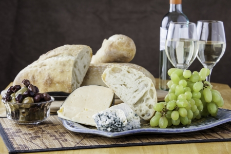 Rustic bread arrangement with assorted olives, cheeses and grapes with a glass of wine