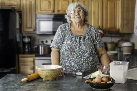 Grandmother or mother in the kitchen by baking supplie with a big smile as she gets ready to bake.