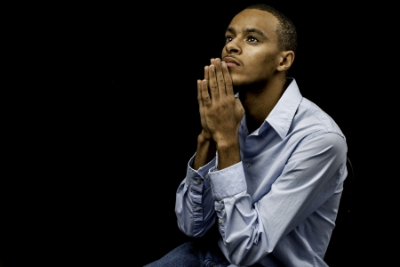 christian faith: Nice isolation of a young african american black male praying with plenty of space for custom text
