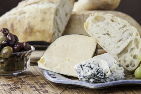 Platter of assorted cheese with rustic bread, olives and grapes