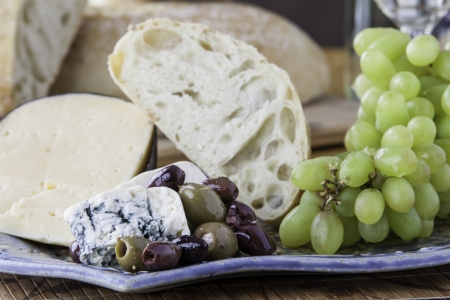 Close up of a tray of assorted rustic bread and cheese with olives and grapes Stock Photo