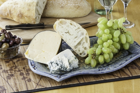 Rustic bread and cheese platter with grapes and wine photo