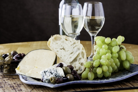 Rustic bread and cheese platter with grapes and wine
