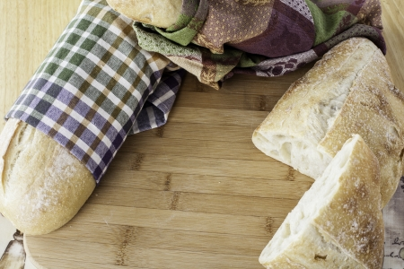 whole rustic bread wrapped in kitchen towels on cutting board with space for your personal text