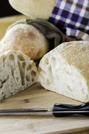 Rustic bread wrapped in kitchen towels with one sliced on a cutting board