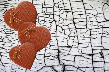 Three valentine's day heart shaped boxes against a cracked peeling wood background photo