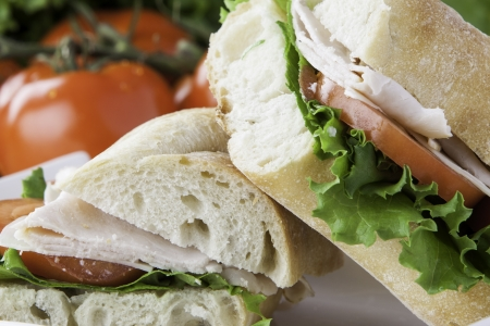 close up of a cut turkey sub with tomato, lettuce and cheese