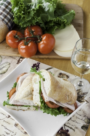 Turkey sub on rustic bread with tomato, bread, lettuce and cheese overhead view