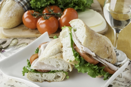Turkey sub on rustic bread with tomato, bread, lettuce and cheese in the background