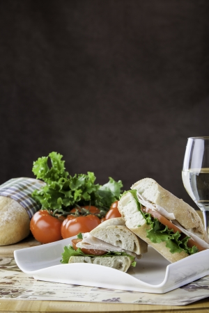 Turkey sub on rustic bread with tomato, bread, lettuce and cheese in the background with space for personal text Stock Photo