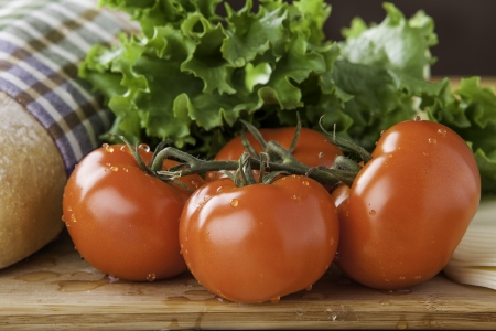 close up of tomato with loaf of rustic bread, lettuce and cheese