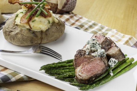 asparagus bed: rare sliced new york strip steak on a bed of asparagus with twice backed potato