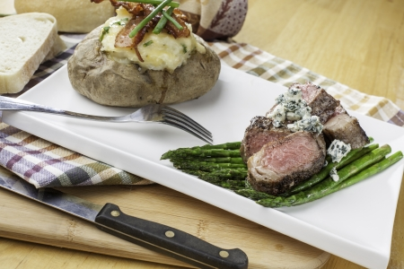 rare sliced new york strip steak on a bed of asparagus with twice backed potato