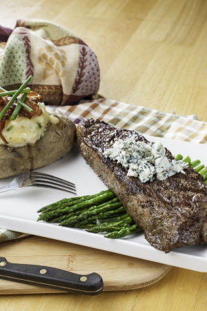 twice: Rare new York strip steak on asparagus topped with bleu cheese with bread and twice baked potato